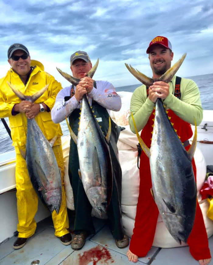 3 men holding offshore catches