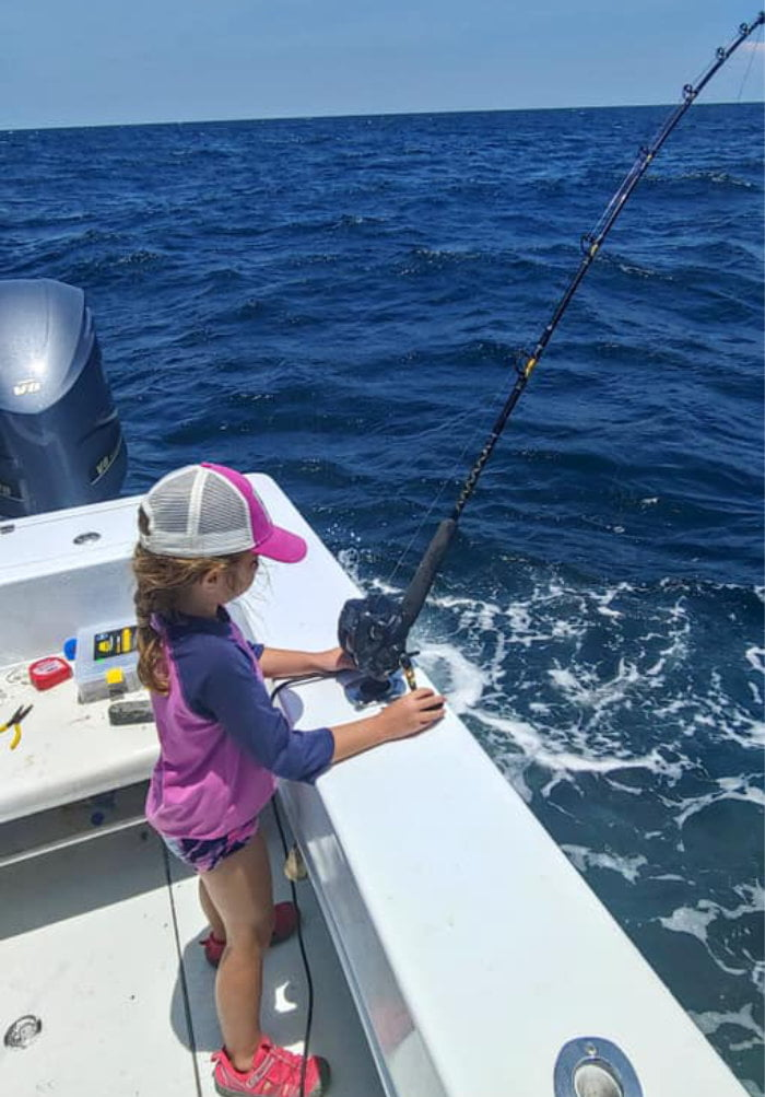 Small girl fishing offshore